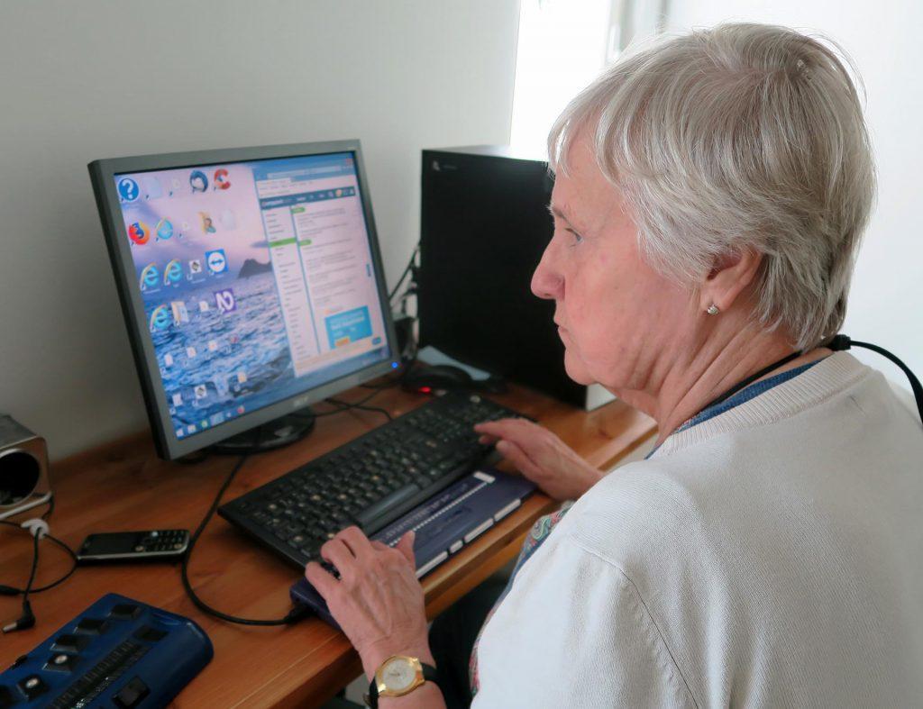 Kuvassa tietokoneen käyttäjä, joka käyttää tietokonetta pistenäytön avulla. Kuva on otettu vasemman olkapään takaa. Henkilön edessä pöydällä ovat pistenäyttö ja sen takana näppäimistö. Näppäimistön takana on näyttö. Tietokoneen keskusyksikkö on pöydän oikeassa reunassa. Henkilön kädet ovat pistenäytöllä lukemassa ja näppäimistöllä ohjaamassa kohdistinta.