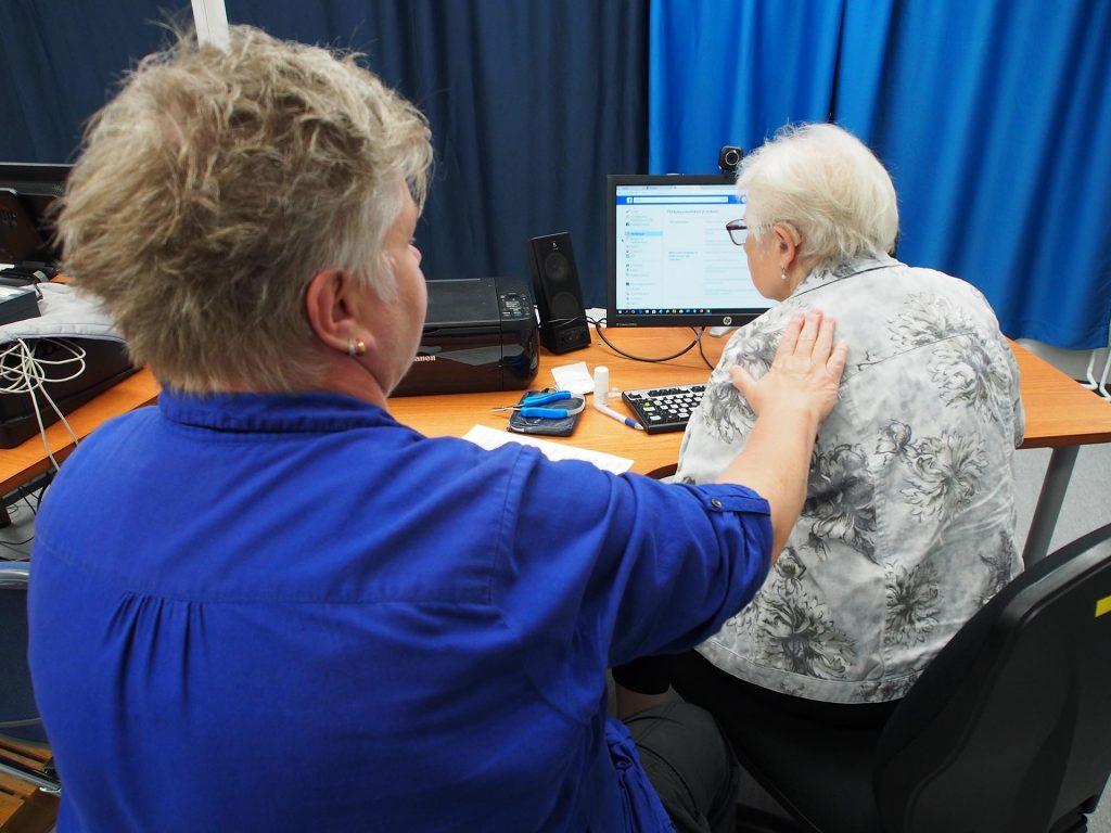 ICT-ryhmäkoulutuksessa apukouluttaja ohjaa oppilasta kehon kautta.