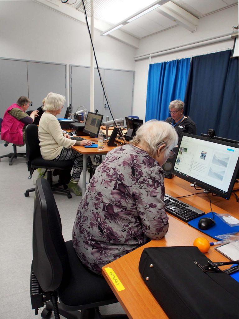 ICT-ryhmäkoulutustilanteessa pääkouluttaja vetää opetusta ja apukouluttaja tukee oppilaita kehon kautta selän takaa.