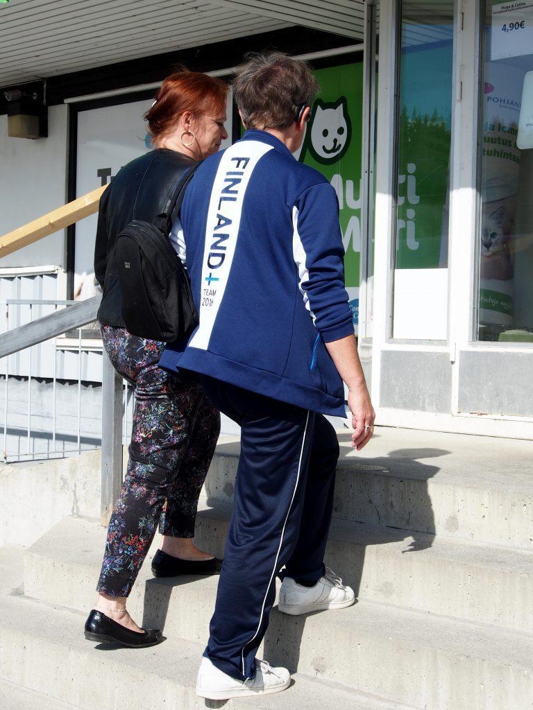 Hoitajat opastavat ja auttavat asiakkaita asiointikäynneillä. Kuvassa on menossa asiakkaan työntekijän kanssa portaita pitkin eläinkauppaan.