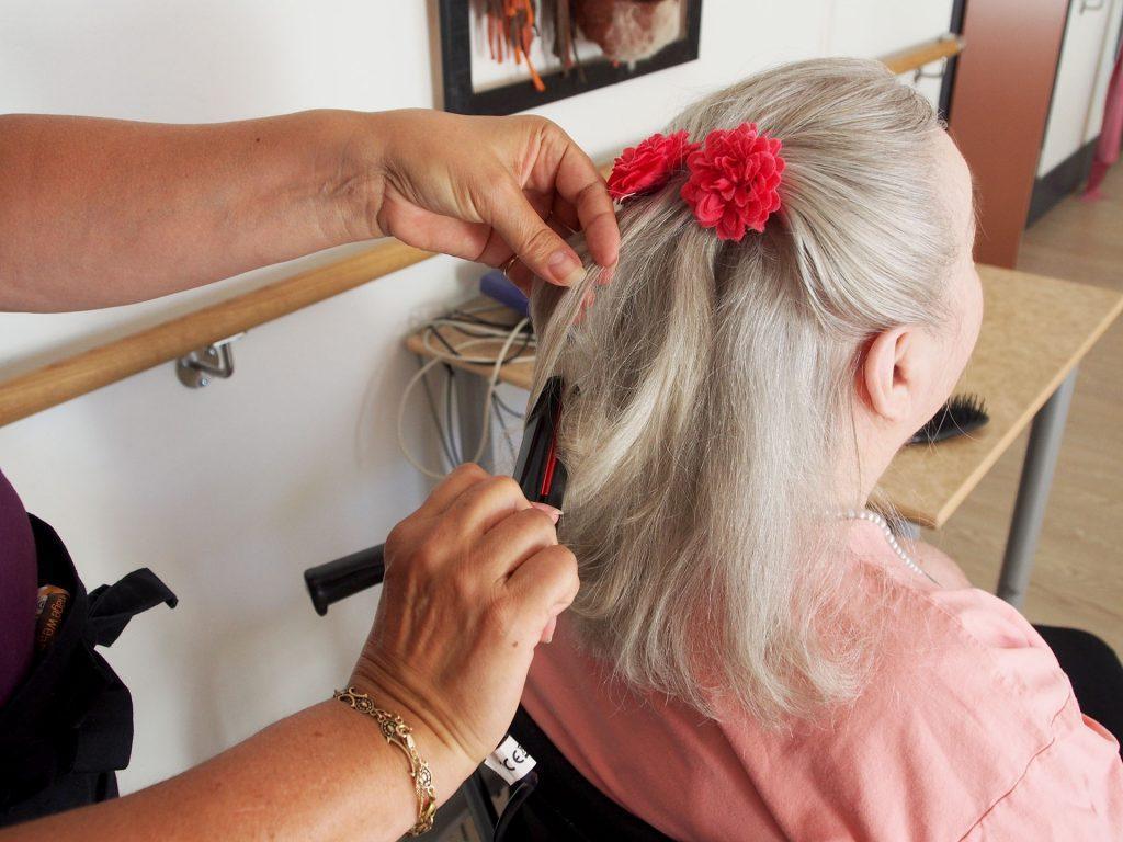 Hoitaja letittää asiakkaan hiuksia aamutoimien yhteydessä. Asiakkaan hiuksiin on laitettu upea punainen kukka.