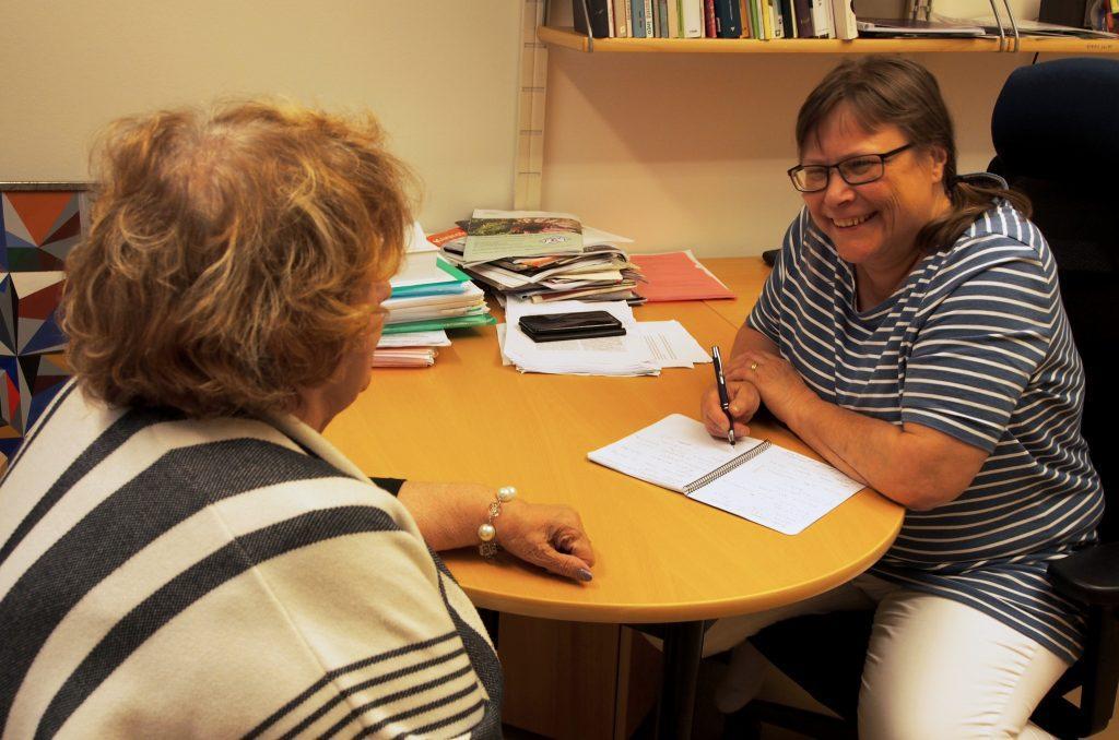 Aluepalvelut tukee asiakkaita kuulonäkövammaan liittyvässä palvelutarpeen selvittämisessä. Kuvassa asiakas keskustelee palveluasiantuntijan kanssa pöydän ääressä. Joskus arjessa on kommelluksia, joka naurattaa molempia.