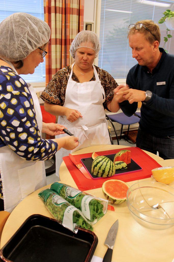 Kurssilainen tutustuu uusiin ruoanlaiton työvälineisiin tulkin avustuksella. Vieressä ohjaaja esittelee työvälineitä.