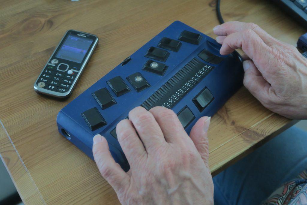 Kuvassa on yläpuolelta katsottuna pieni pistenäyttö, joka on yhdistettynä matkapuhelimeen langattomasti. Sen vieressä on tähän yhdistetty näppäinpuhelin. Pistenäytöllä ohjataan puhelimen toimintoja ja luetaan mitä näytöllä näkyy. Matkapuhelimen muutama painike on merkittynä kohotarroilla käytön helpottamiseksi.